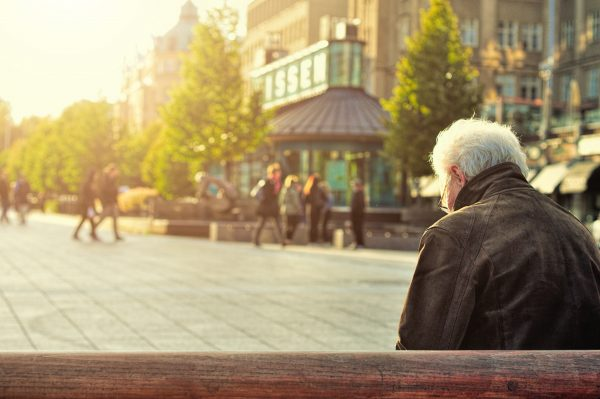 Retired man sitting on bench at building